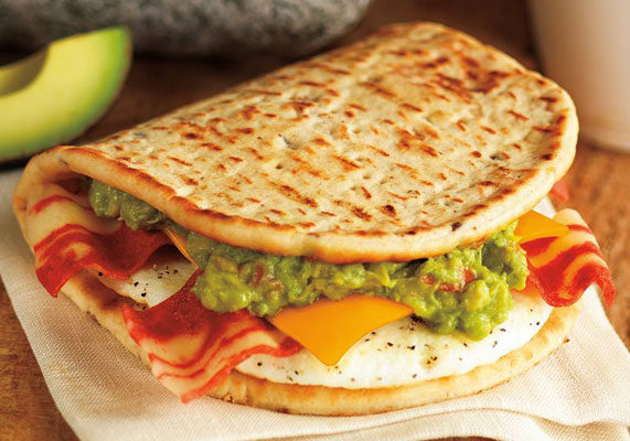 Dunkin' Donuts has added guacamole to its breakfast menu with the new Bacon Guacamole Flatbread Sandwich. It features two strips of bacon, egg, a slice of reduced fat cheddar cheese and guacamole made with Hass avocados, cilantro and lime juice. The Bacon Guacamole Flatbread Sandwich will be available through May.