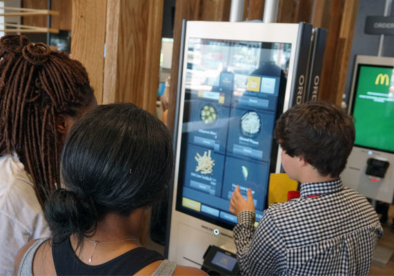 """At the front of the store are several digital kiosks, where customers may order a personalized burger or sandwich with the help of a bowtie-clad employee, known here as a """"concierge."""" Toppings not found in a traditional McDonald's include guacamole, pico de gallo, maple bacon, creamy dijon, sriracha mayonnaise and grilled tomato. (1 of 12)"""