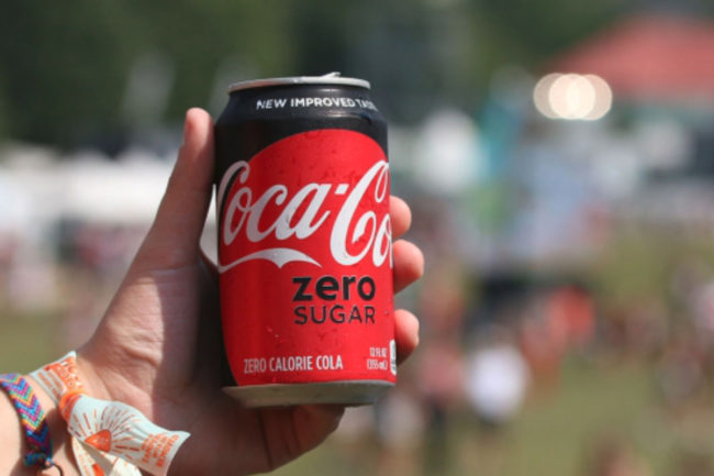 Millennial drinking Coke Zero Sugar at a music festival