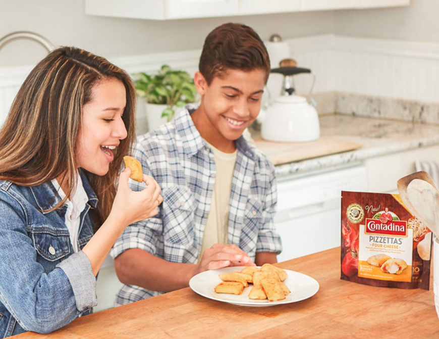 Two teens eating Contadina Pizzettas