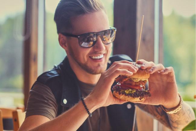 Millennial eating plant-based burger