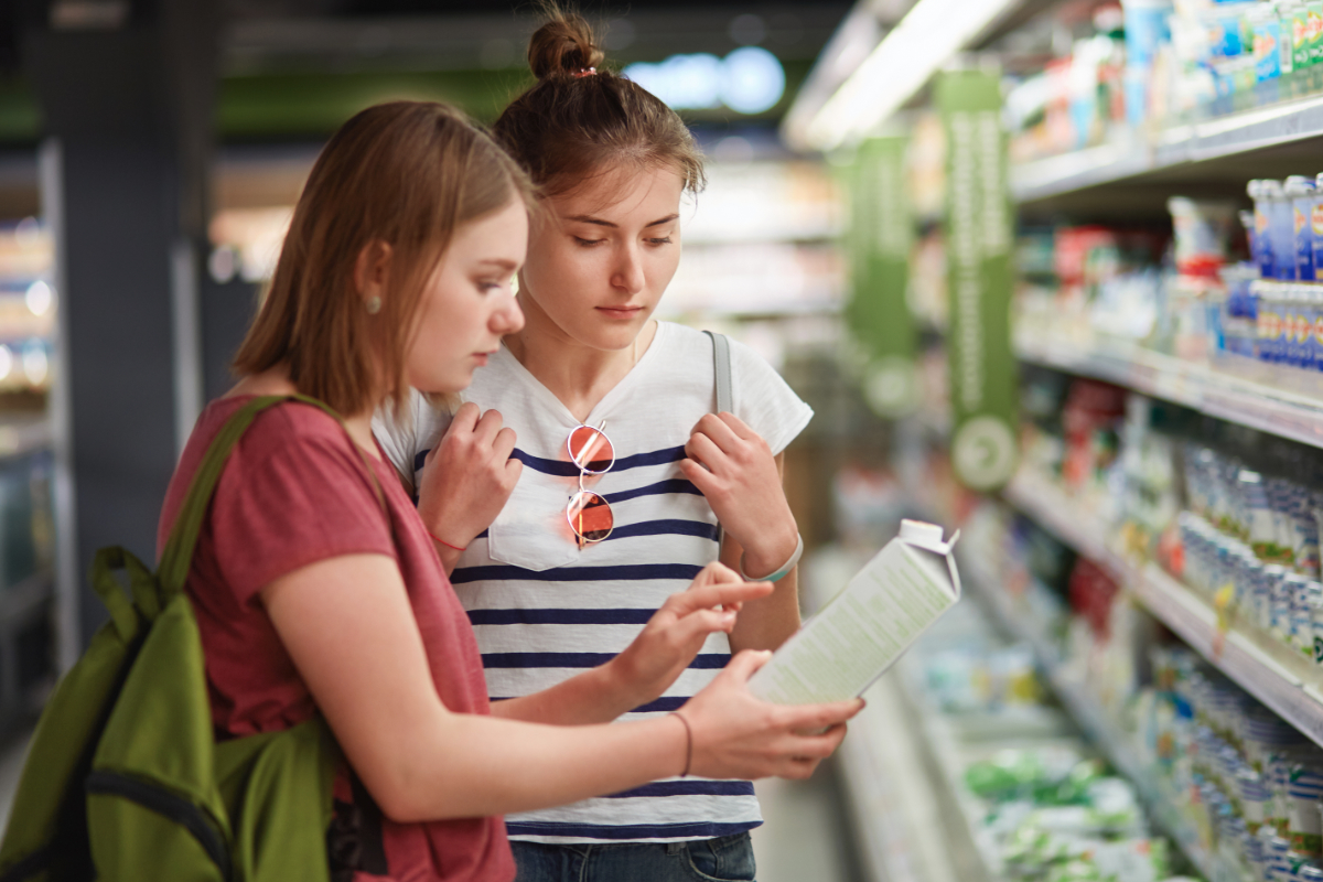 Gen Z consumers reading food label at supermarket