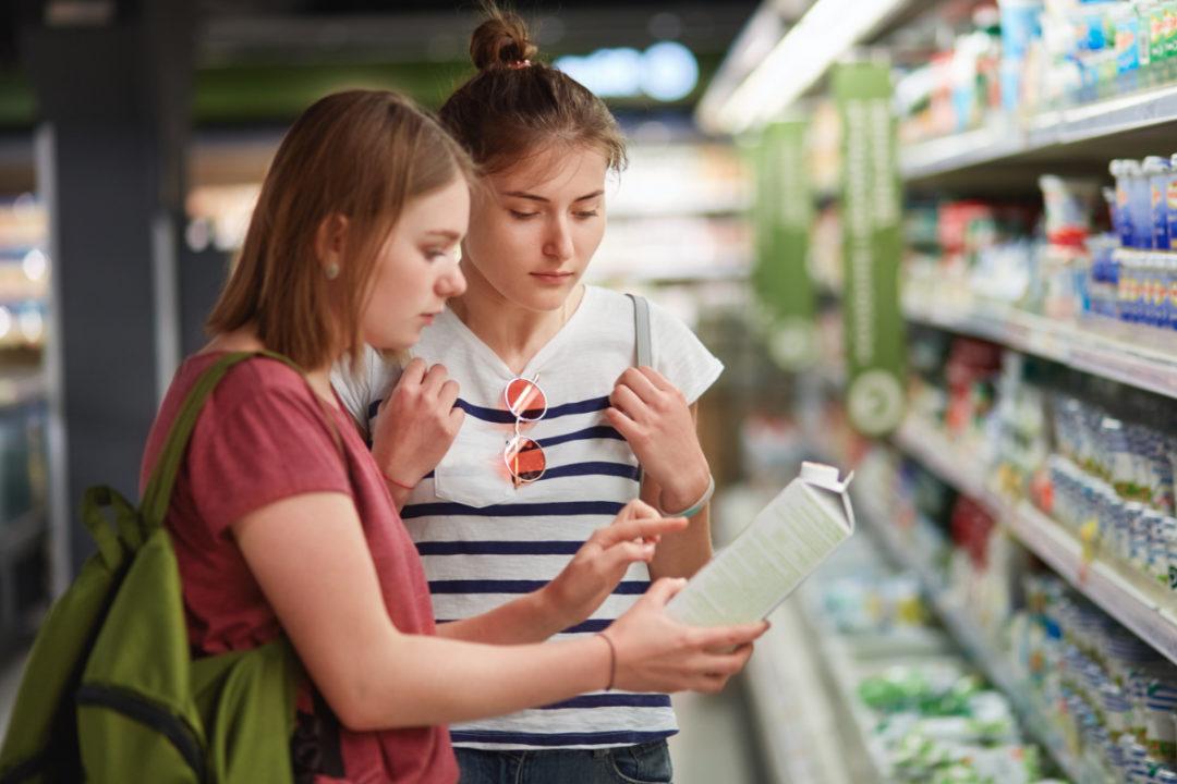 Gen Z consumers reading food label at supermarket