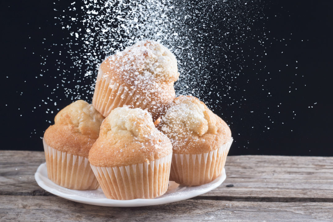 Sugar pouring onto muffins