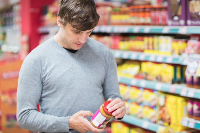 Man looking at nutrient content claim on peanut butter in supermarket