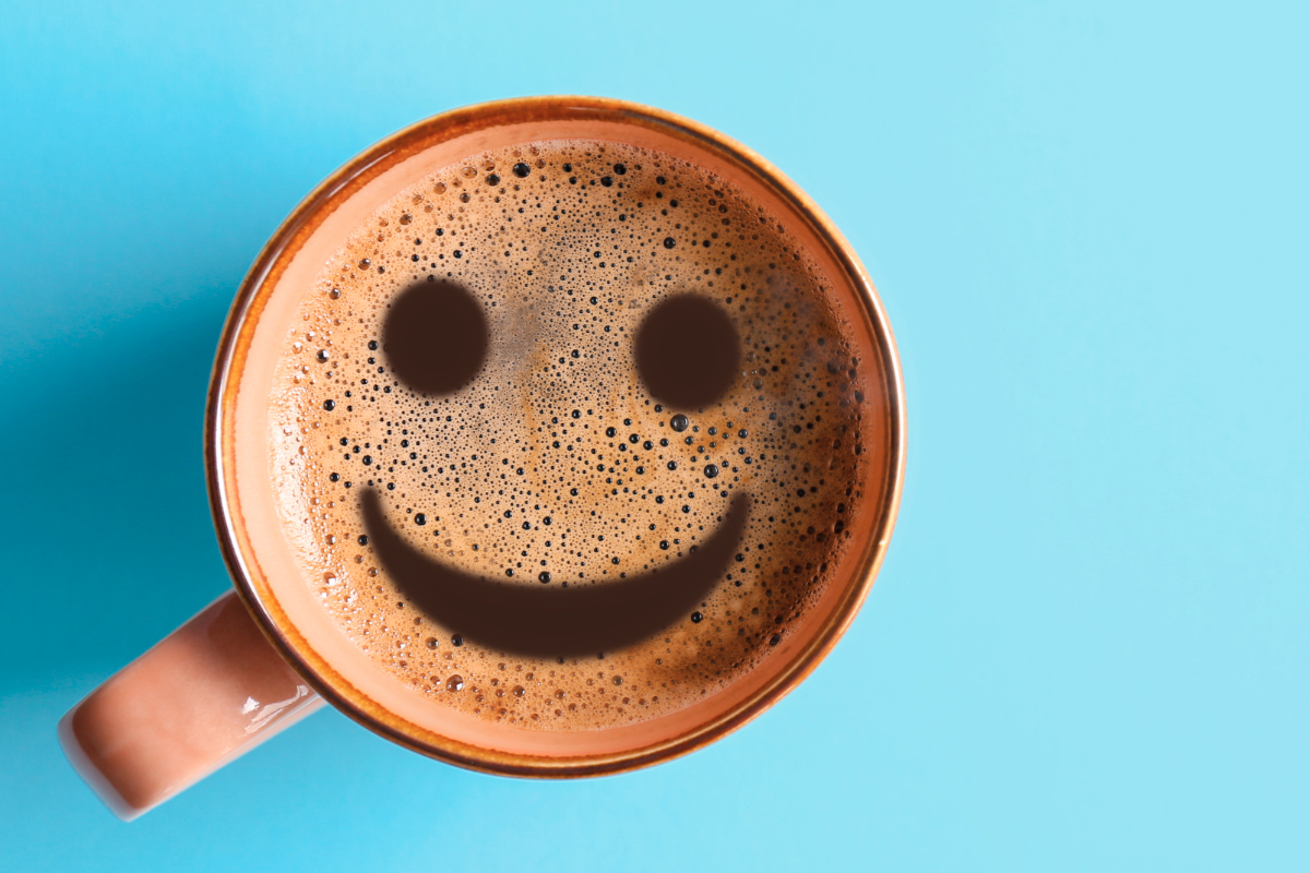 Cup of coffee with happy face in foam