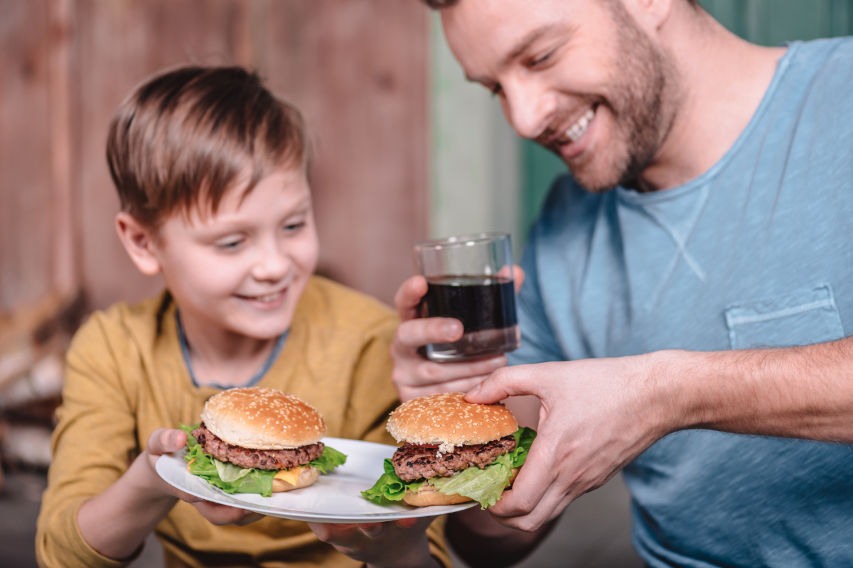 Father and son eating burgers at home