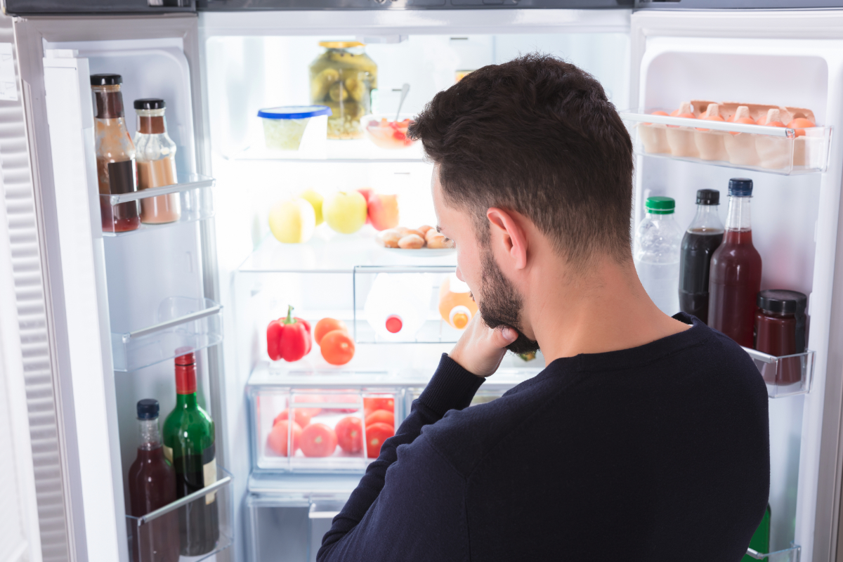 Man looking in fridge wondering what is for dinner