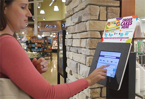 Woman using DecoPac digital cake ordering kiosk