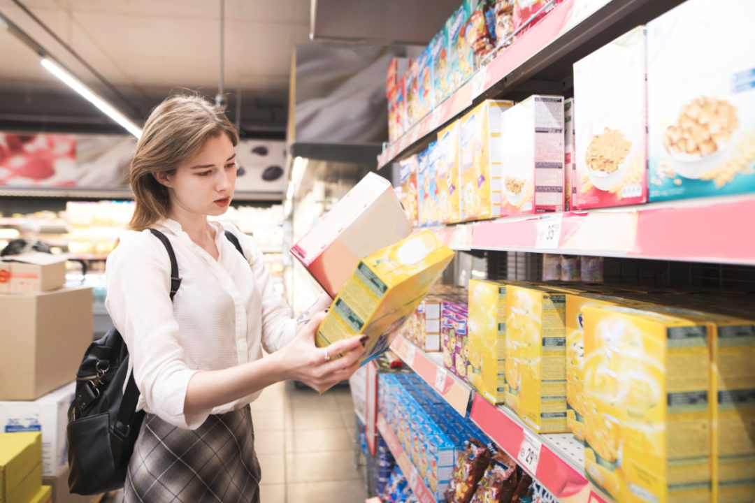 Woman reading cereal box labels in supermarket
