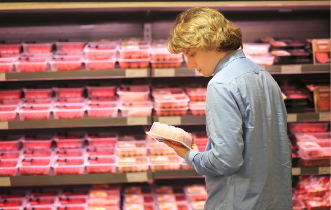 Man shopping for meat at grocery store