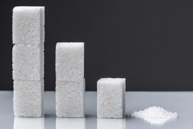 The downward chart is made up of sugar cubes and granulated sugar. Sugar reduction in consumption ?oncept.