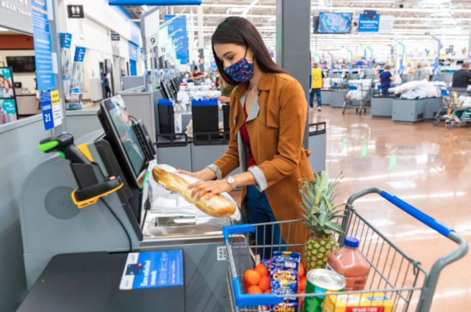 Woman wearing face mask buying groceries at a Walmart self check station