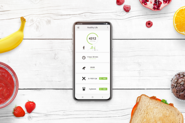 Phone on desk surrounded with food. Healthy life app concept with daily number of steps, number of calories burned, number of calories consumed
