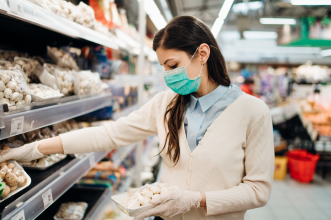 Woman with mask safely shopping for groceries amid the coronavirus pandemic
