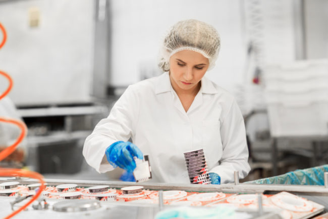 Woman working on ice cream manufacturing line