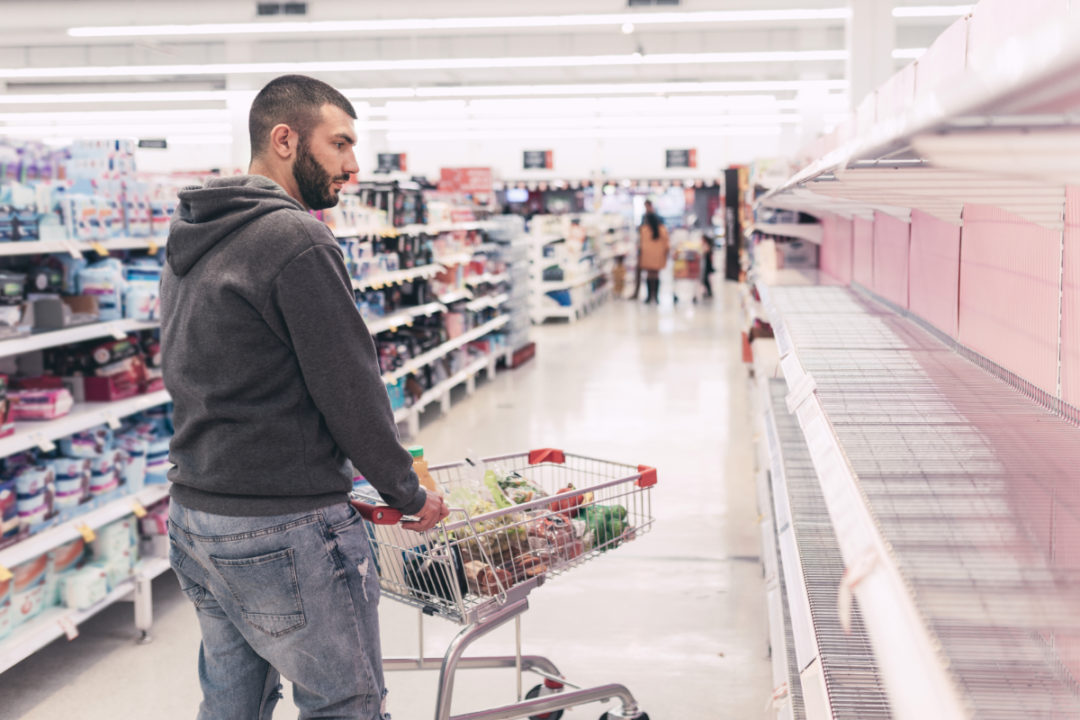 Man staring at empty supermarket shelves