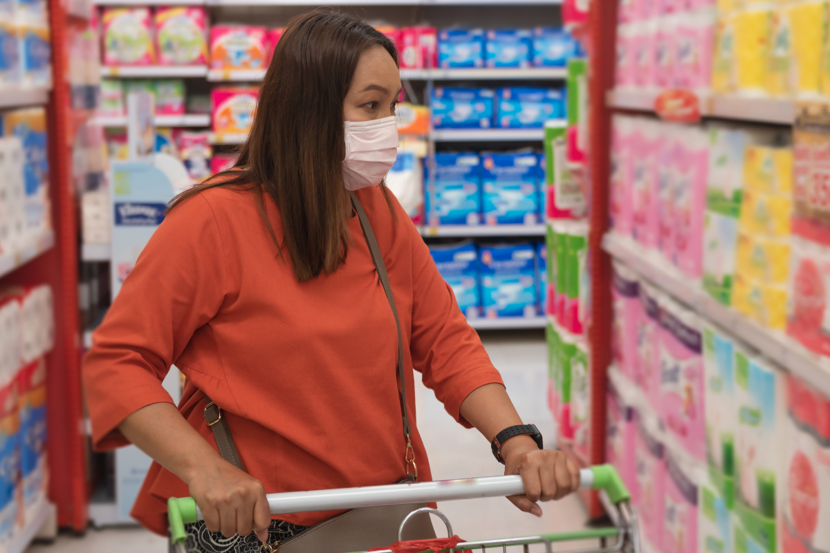 Woman grocery shopping while wearing face mask