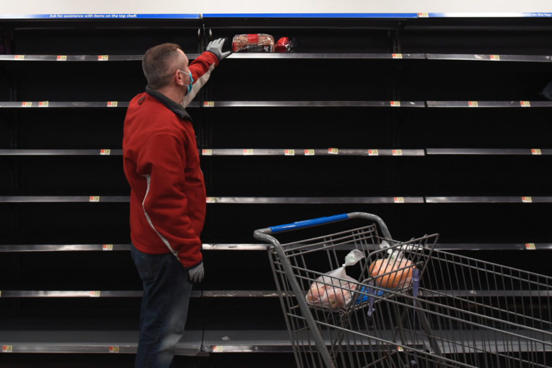 Man shopping for bread amid empty shelves due to coronavirus