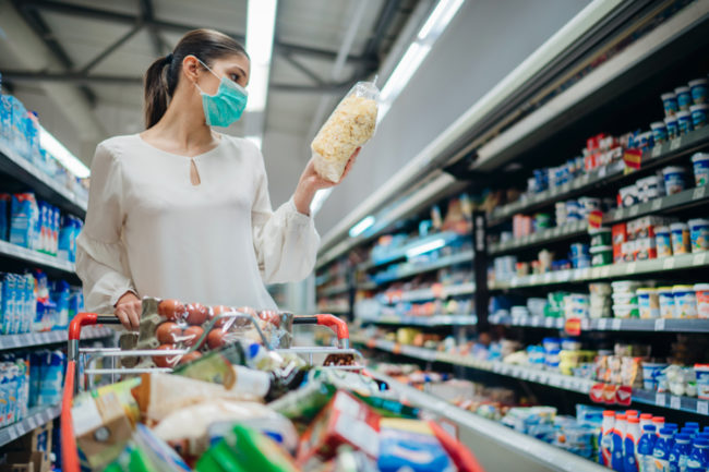 Woman grocery shopping while wearing mask