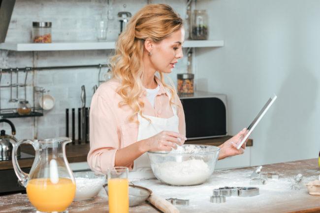Woman reading baking recipe at home