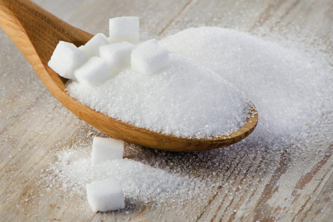 Wooden spoon full of sugar and sugar cubes