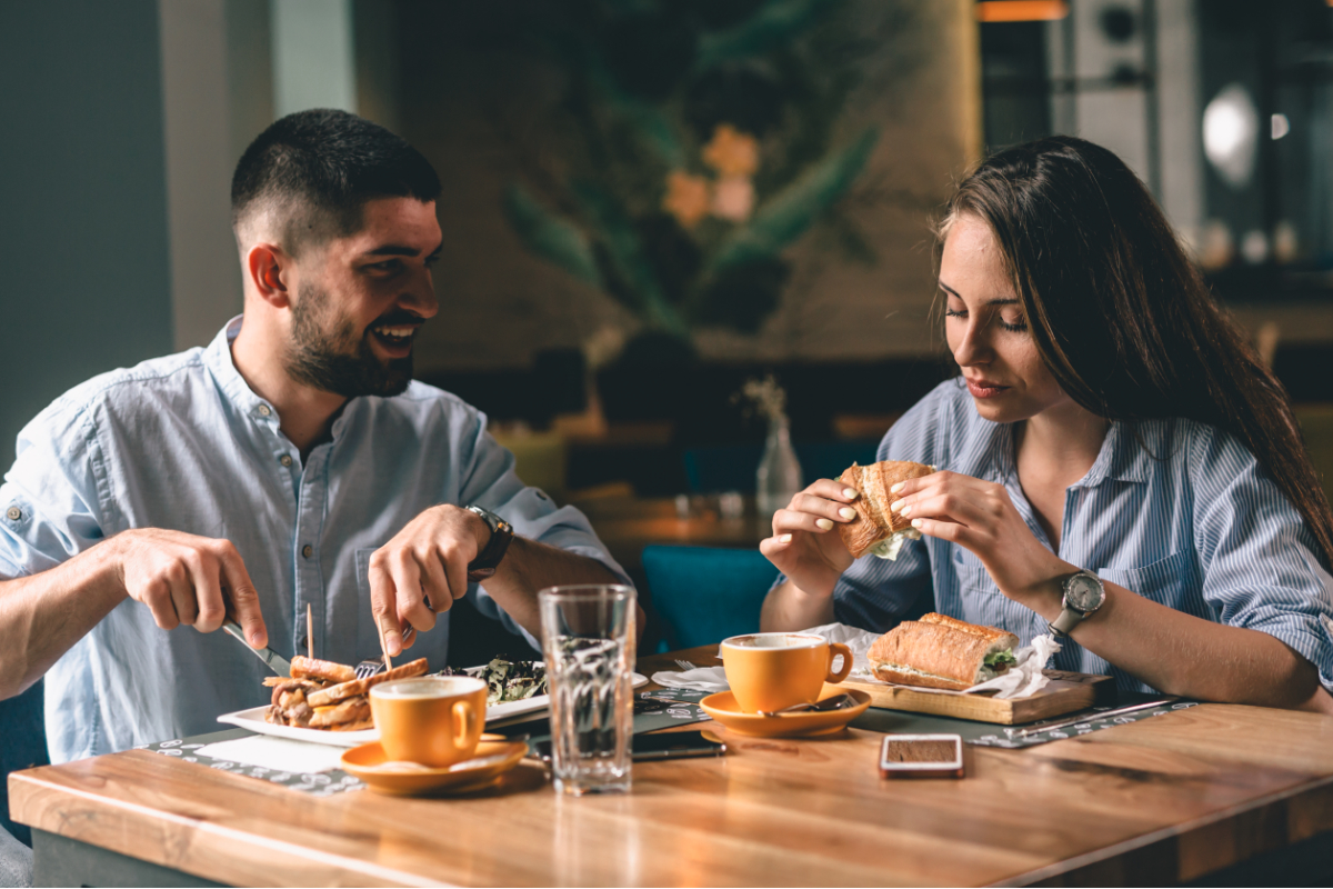 Couple eating at restaurant with full attribution