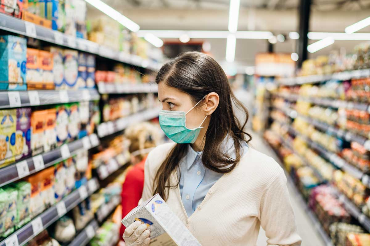 Masked woman shopping for snacks
