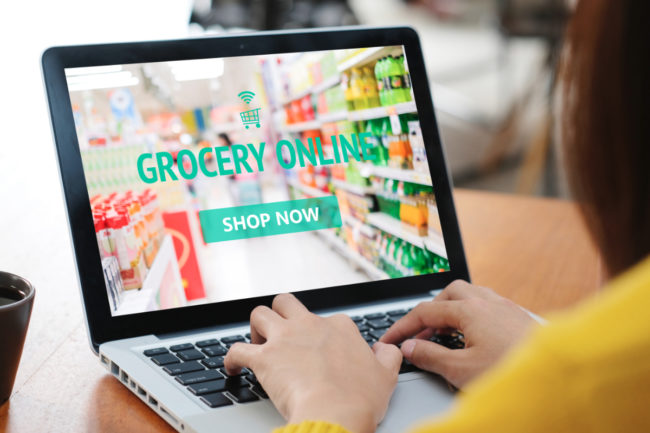Woman grocery shopping online via laptop