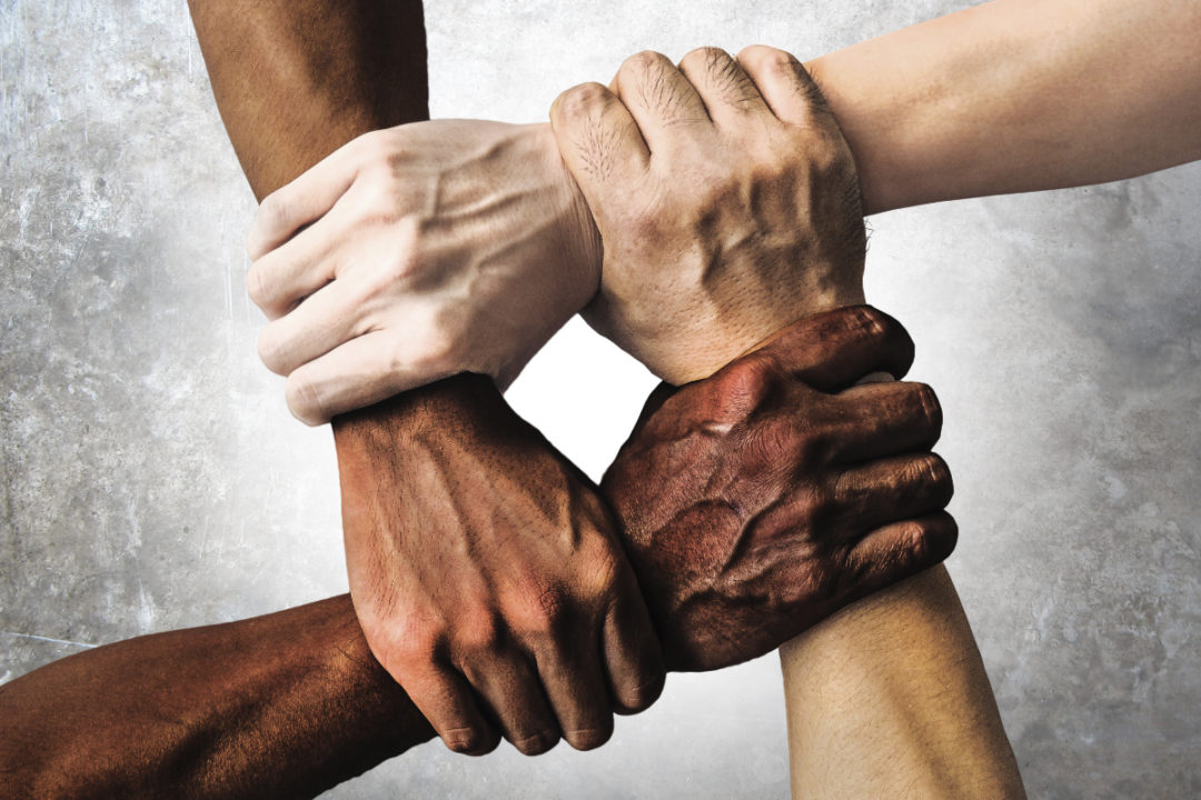 Multiracial hands linked together