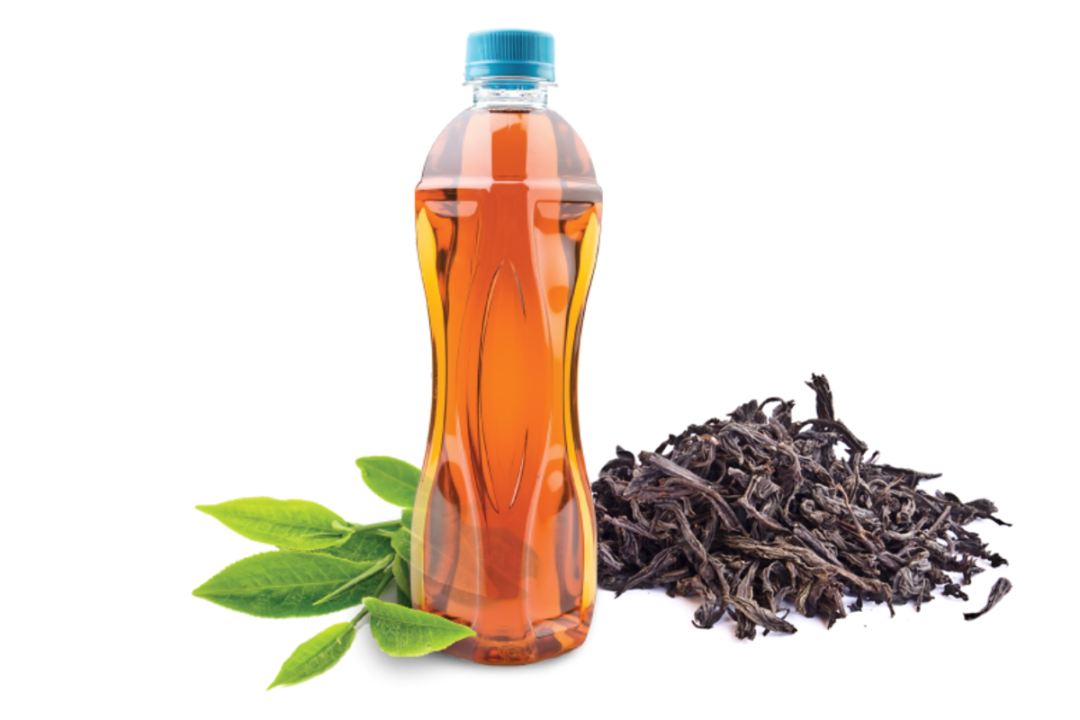 Tea bottle next to tea leaf and dried tea extract