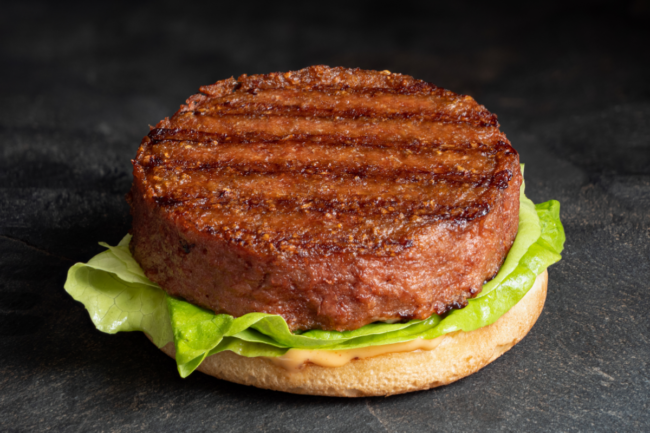 Freshly grilled plant based burger patty on bun with lettuce and sauce isolated on black countertop