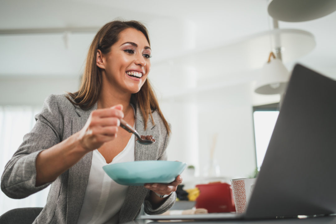 Woman eating in front of a laptop