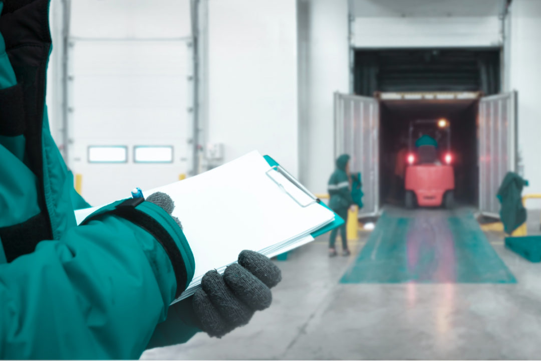 Staff worker with clipboard checking goods and Safety Officer for dangerous in Cold room storage and freezing warehouse.