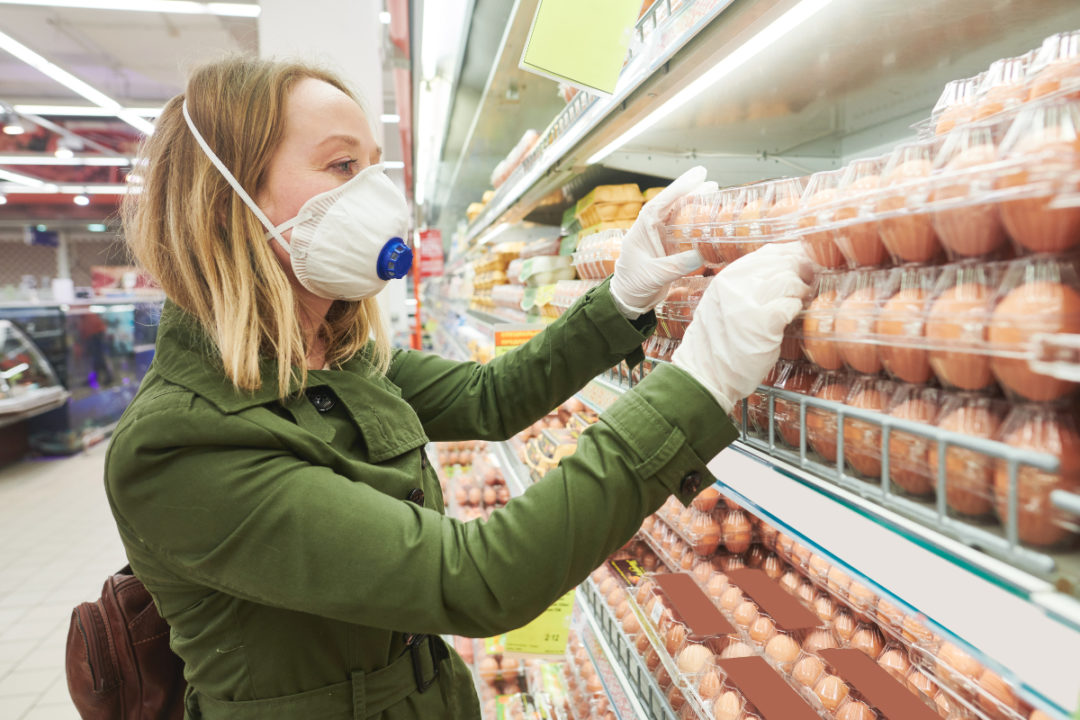 Woman shopping for eggs while wearing face mask and gloves during COVID-19 pandemic