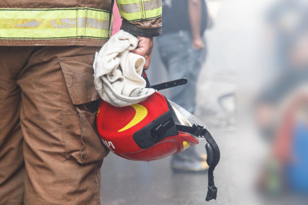 Firefighter holding his helmet
