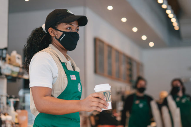 Starbucks barista wearing a mask giving a customer coffee