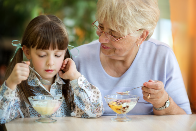 child and grandmother eating yogurt
