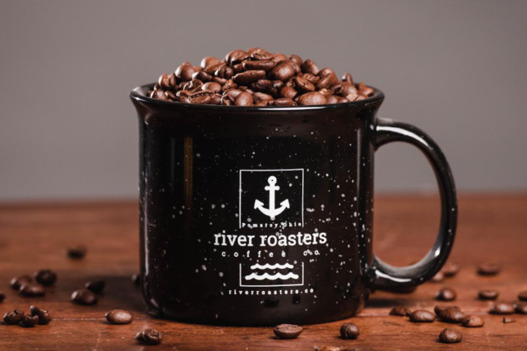 coffee cup filled with coffee beans featuring River Roaster Coffee's logo
