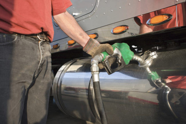Man fueling up a transport truck