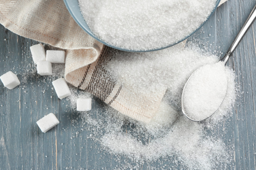 Bowl and spoon with sugar on wooden background