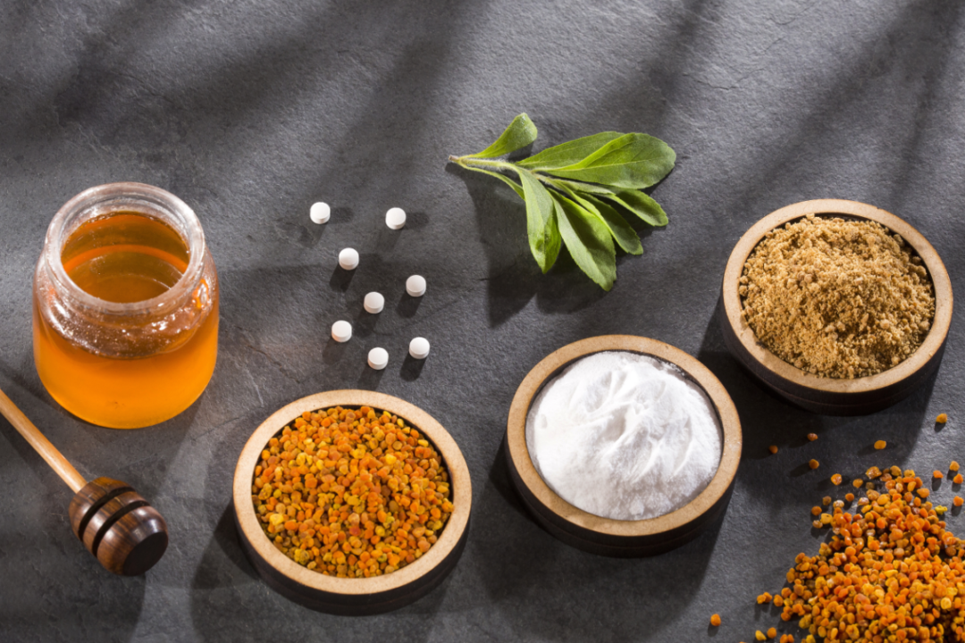 Variety of natural sweeteners - Pollen, honey, sugar and stevia leaves