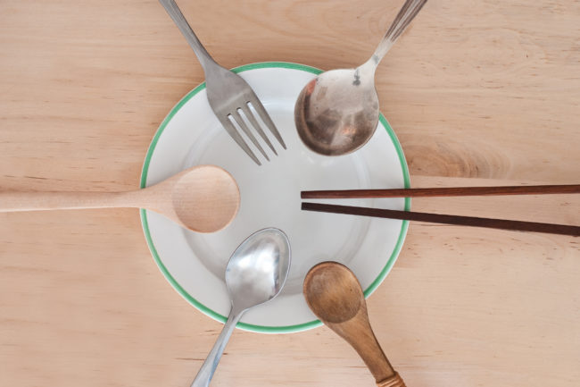 Bowl with utensils from around the world resting on it