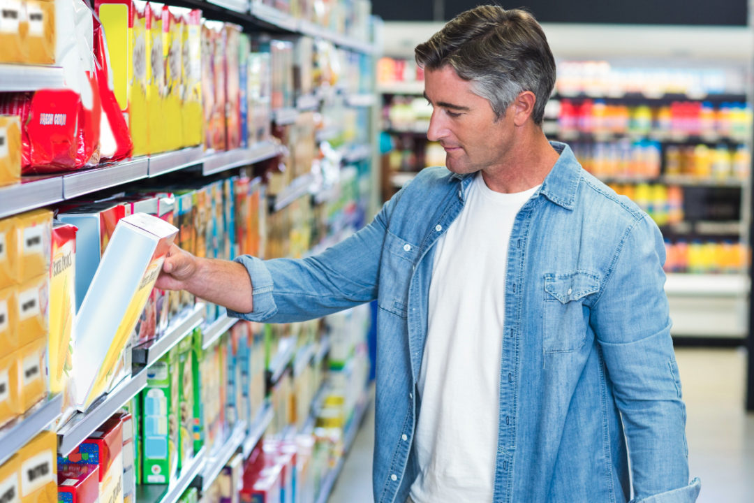 Man choosing cereal at the grocery store