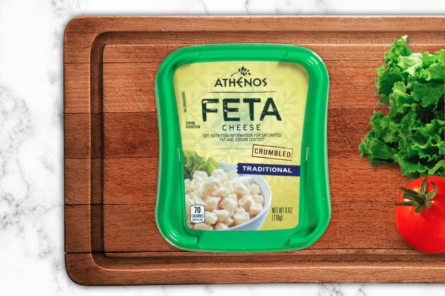 Athenos feta cheese on a cutting board with lettuce and tomato