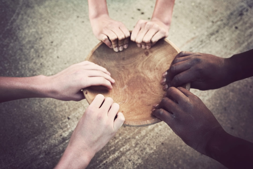 Hands of hungry people holding empty food bowl