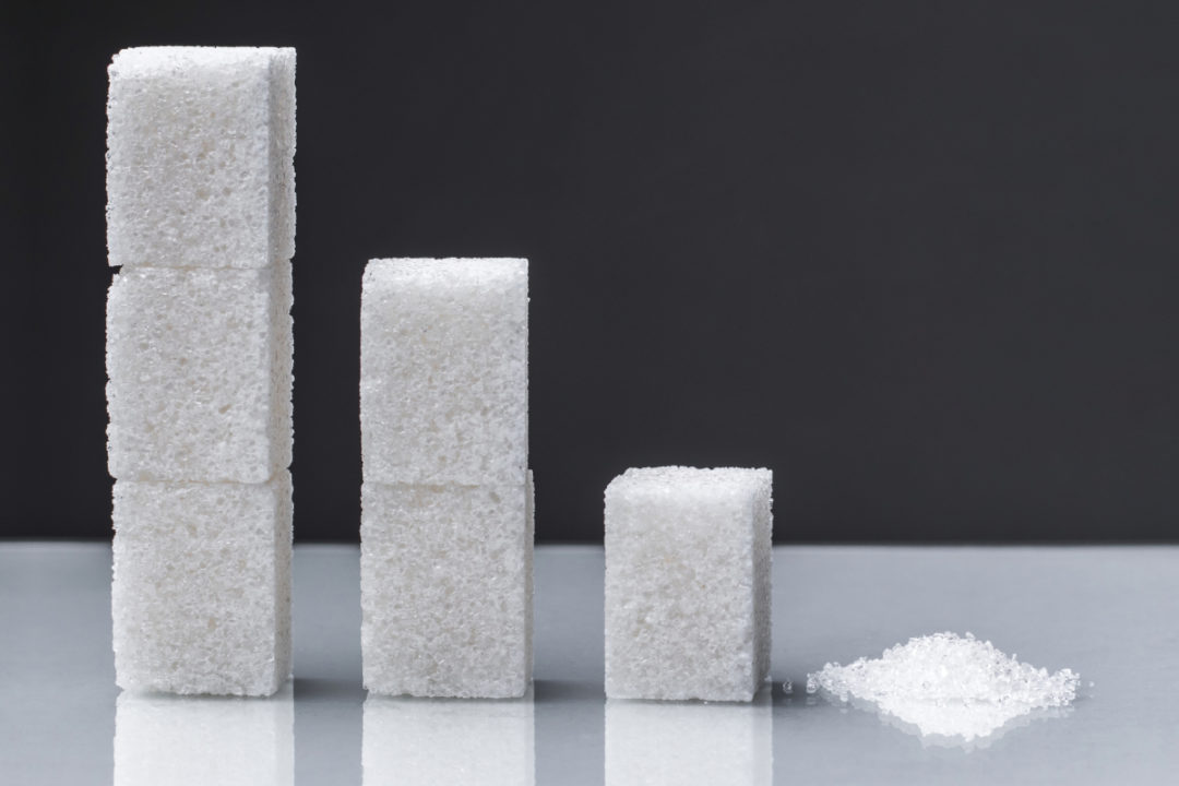 Stacks of sugar cubes descending into a small pile of sugar - sugar reduction concept