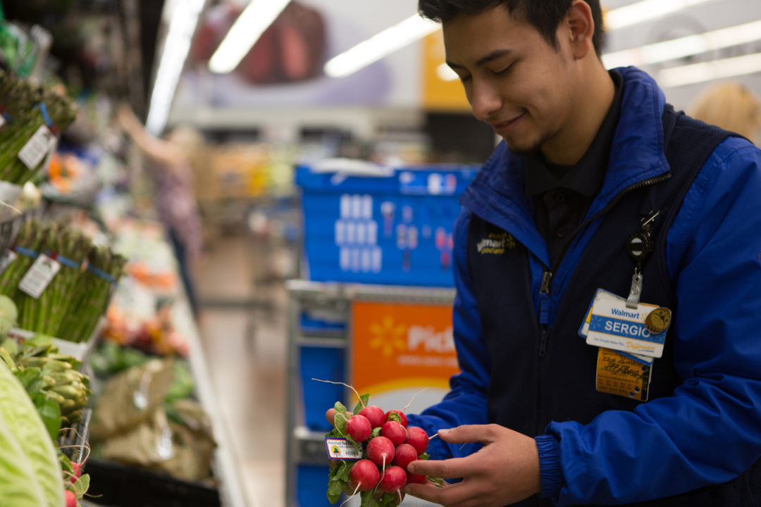 Walmart associate picking produce