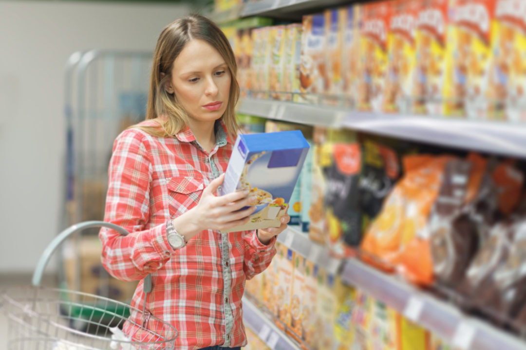 Woman reading food label, concerned