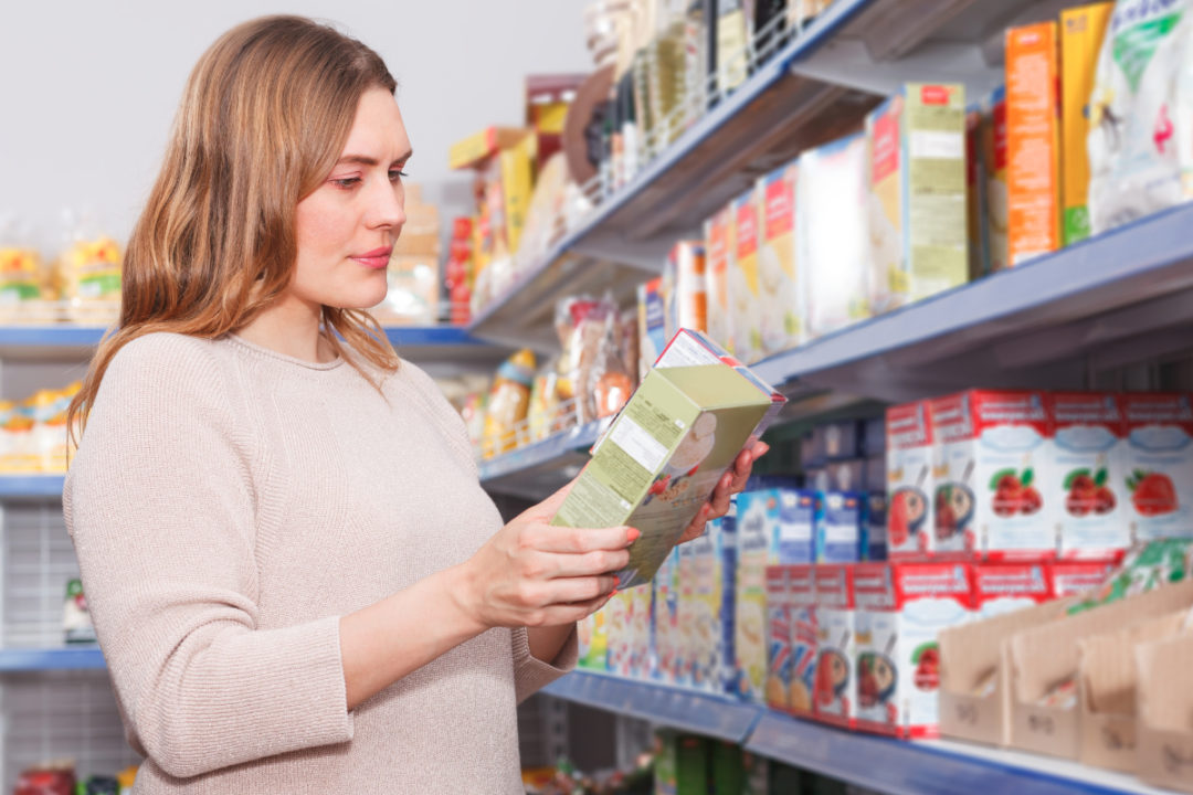 Woman reading food label in grocery store
